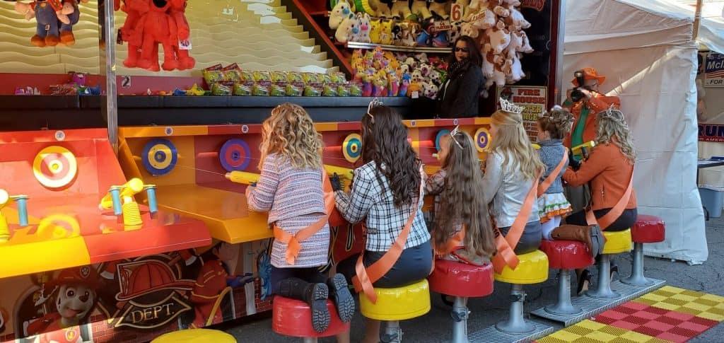 Miss Pumpkin Show kneeling down to talk with Little Miss